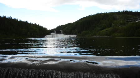 waterfall cascading into pool : beautiful summer landscape with waterfall, river flow and hydro electrical dam water gates in the far background