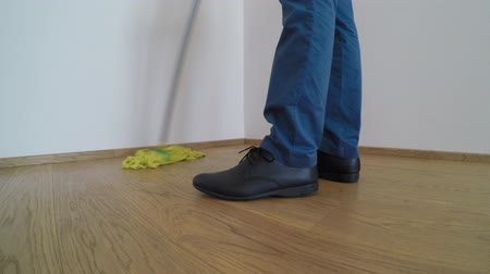 швабра : Man wearing blue shoes and trousers, washes the parquet floor with the yellow mop