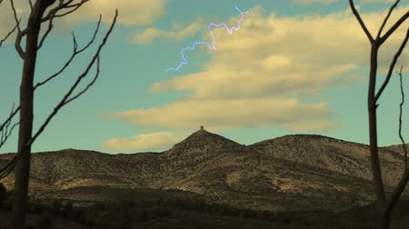 roussillon : Isolated tower on arid hills with lightning in the sky