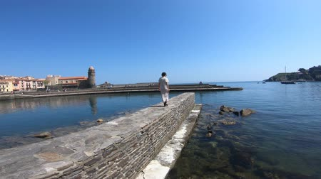 roussillon : young woman in a dress walking on the dock of a port at the Mediterranean sea in Collioure , Pyrenees Orientales in the south of France Stock Footage