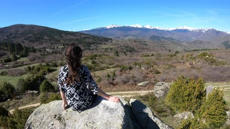 ariege : young woman alone perched on a rock observing the pyrenean mountains, Occitanie in southern of France
