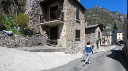 occitania : single woman walking in the streets of a pyrenean village, Aude in southern of France
