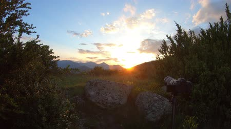 SLR camera on a tripod making a time lapse during a sunset in Pyrenees, France