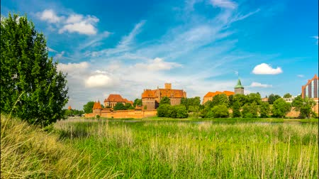 4K - timelapse. View of a medieval castle in Malbork with a reflection in the river.