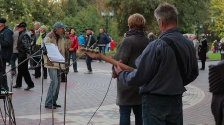 contato com os olhos : Chernihiv, Ukraine 22 spt 2019. Singer and bass guitar player are performing at the retiree dancing party in the park Vídeos
