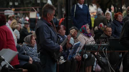 bámul : Chernihiv, Ukraine 22 spt 2019. Bass guitar player is performing at the retiree dancing party in the park Stock mozgókép