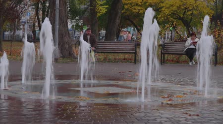discutir : Chernihiv, Ukraine. 13 oct 2019. Man and woman sitting on separate benches in the park near the fountain