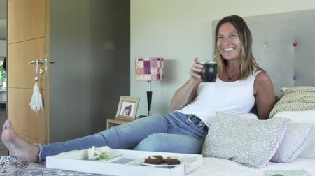 латина : Woman having breakfast and drinking mate in bed while watching TV
