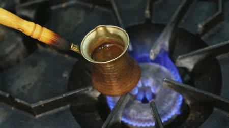 kabine : Making turkish cofee in copper cezve over gas stove.