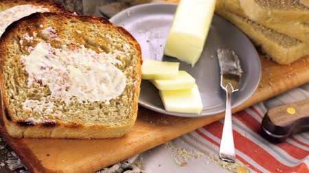 vaj : Toasted slices of freshly baked sourdough bread with butter. Stock mozgókép
