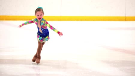skate : Young figure skater practicing at indoor skating rink.
