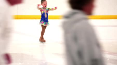 patenci : Young figure skater practicing at indoor skating rink.