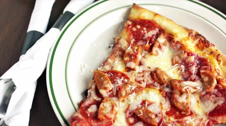 crust : Fresh pepperoni and sausage pizza slice on the table in Italian restaurant.
