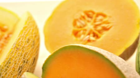 miniatűr : Variety of organic melons sliced on wood table.