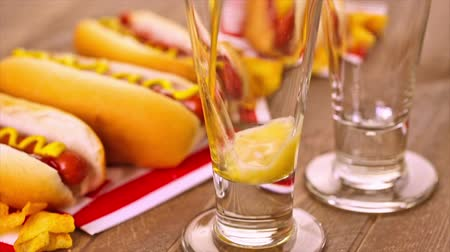 sekaná : Grilled hot dogs with mustard and ketchup on the table with draft beer.