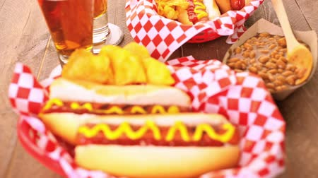 alkol : Grilled hot dogs with mustard and ketchup on the table with draft beer.