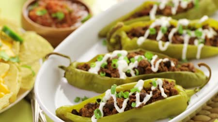 pimentas : Chipotle beef  bean stuffed chili peppers garnished with sour cream and scallions.