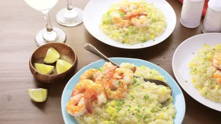 descamação : Homemade corn risotto with roasted shrimp on dining table.