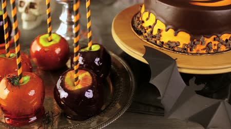 karamel : Table with colored candy apples and cake for Halloween party. Stok Video