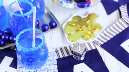 щит : Table set with cocktails and chocolates to celebrate Hanukkah.