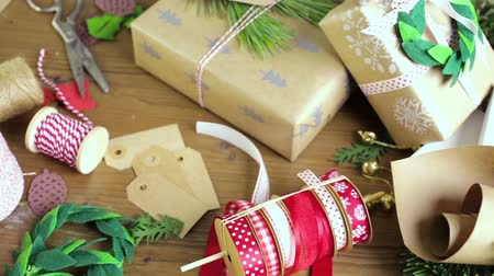 украшенный : Wrapping Christmas gifts in recycled brown paper with vintage style at home.