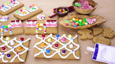pişmiş : Decorating gingerbread house with royal icing and colorful candies.