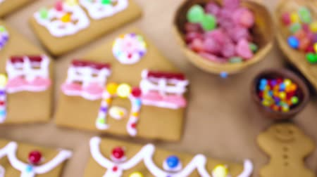 desszertek : Decorating gingerbread house with royal icing and colorful candies.