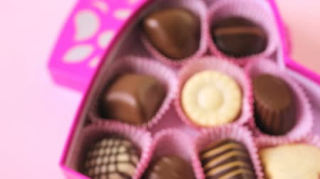 кондитерская : Chocolates in heart shaped box on pink background.