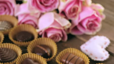 çikolata : Assorted chocolates with pink roses on wood table. Stok Video