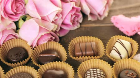sustentável : Assorted chocolates with pink roses on wood table. Stock Footage