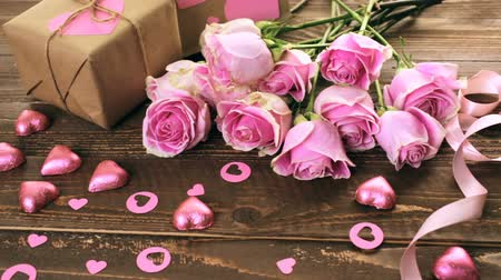 batoh : Pink roses and gift wrapped in recycled paper on rustic wood table.