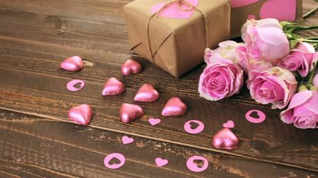 reciclagem : Pink roses and gift wrapped in recycled paper on rustic wood table.