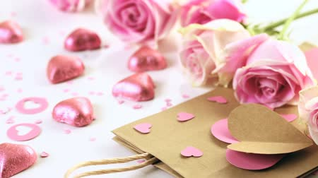 Роуз : Pink roses and hand crafted gift bag on a white background.