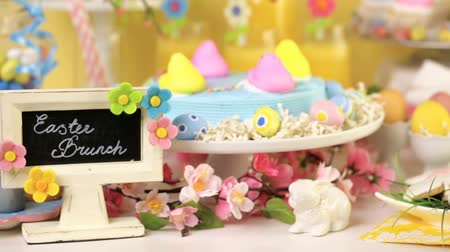 украшенный : Dessert table with Easter cake decorated with traditional Easter marshmallow chicks.