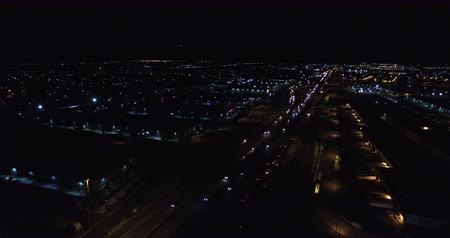 площадь : Aerial view of industrial area next to highway in large city at night.