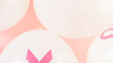 göğüs : White latex balloons with pink ribbons. Stok Video