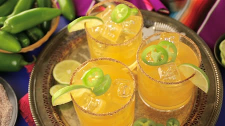 só : Spicy grapefruit margarita cocktail garnished with lime and jalapenos.