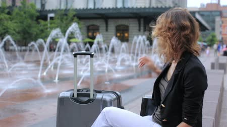 centrum : Young woman in front of the train station with suitcase.