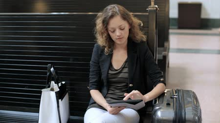 touchpad : Young woman with suitcase waiting for her train inside of the train station. Stock Footage