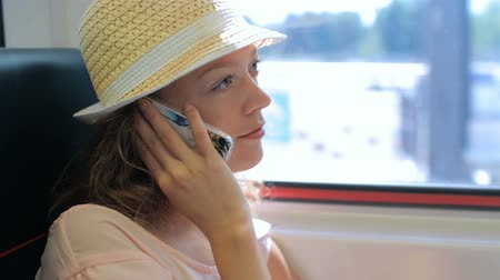 mulher jovem : Young woman talking on the phone while traveling on the train. Vídeos
