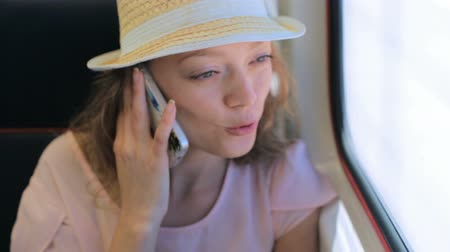 touchpad : Young woman talking on the phone while traveling on the train. Stock Footage