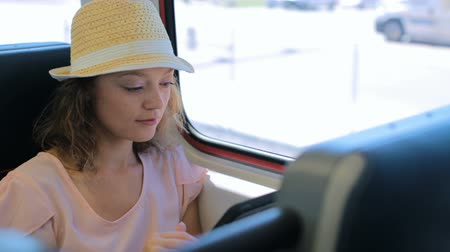 touchpad : Young woman reading book on the tablet while traveling on the train. Stock Footage