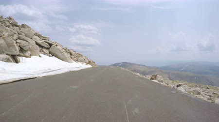 ér : Car driving on paved road above timber line on Mount Evans-POV point of view.