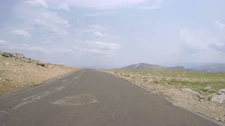 er : Car driving on paved road above timber line on Mount Evans-POV point of view.