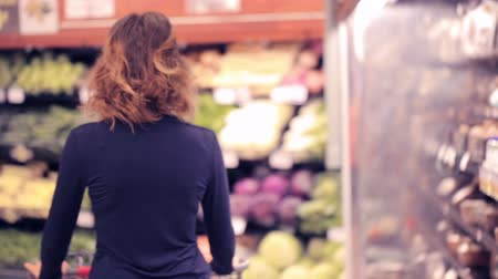 bakkaliye : Young woman shopping in the fresh produce section at the grocery store. Stok Video