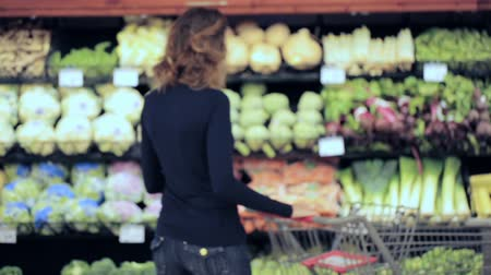 loja : Young woman shopping in the fresh produce section at the grocery store. Stock Footage