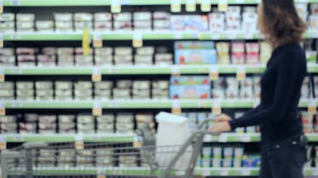 loja : Young woman shopping in the yogurt section at the grocery store.