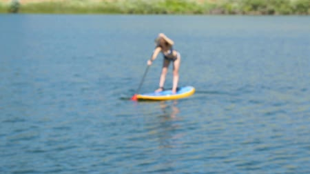 remo : Young woman learning how to paddleboard on small pond. Vídeos