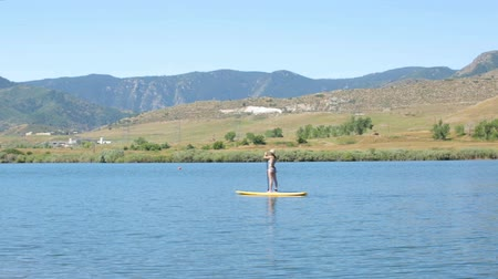 karpatské : Young woman learning how to paddleboard on small pond. Dostupné videozáznamy