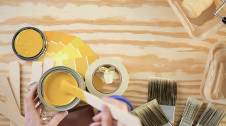 Paint in metal paint can and painters tools on a wood board. Stock Footage
